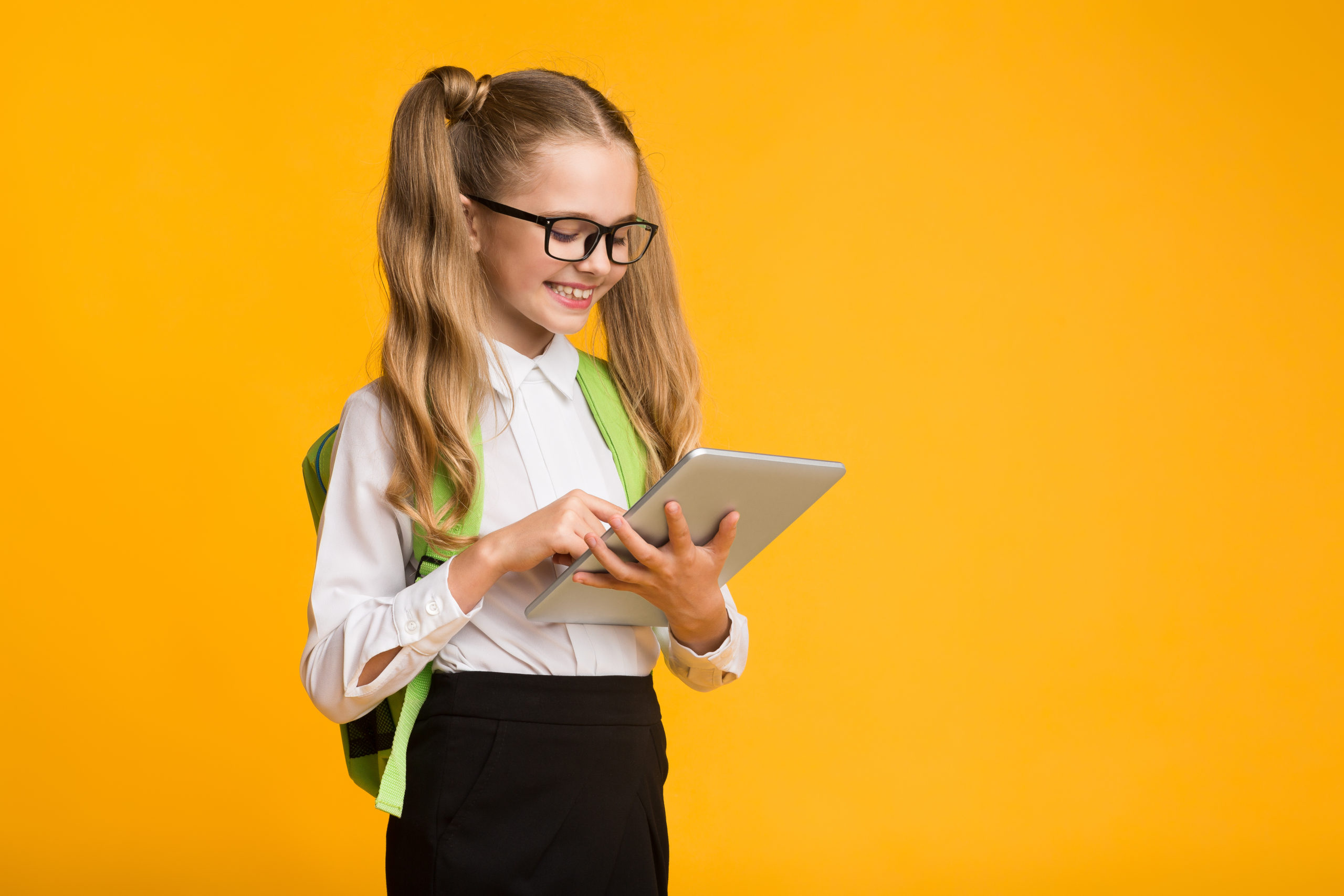 Gadgets And School. Cheerful Schoolgirl Using Tablet Computer Browsing Internet Over Yellow Background. Copy Space